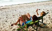 Two women on a beach sit in beach chairs; one is reading a book and the other is gesturing at the waves.