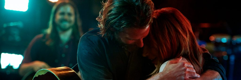 A still image of Bradley Cooper hugging Lady Gaga in A Star Is Born