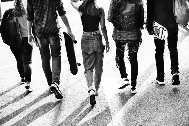 Older teens walking away from the camera in stark black and white